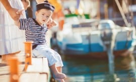 Happy family, mother and son spend time on the pier near the yacht club, they are dressed in striped shirts sailors, the boy wears a hat like a sailor, play and have fun at the dock on summer nature background, blue sea and beautiful boats