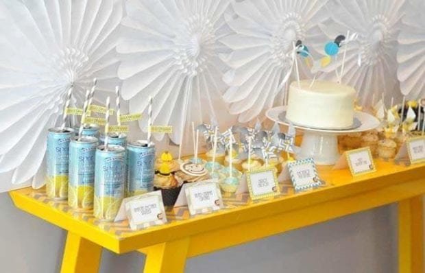 The Curious George dessert table features lots of treats in the blue, yellow, and white color scheme.