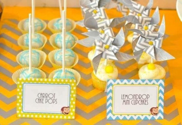 Curious George party foods, including lemon and carrot cake pops, bedecked this dessert table.