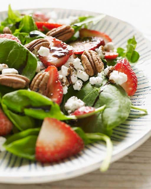 A plate of food on a table, with Salad and Strawberry