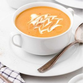 close up shot of butternut squash soup in a soup bowl topped with whipped cream and pumpkin pie spice