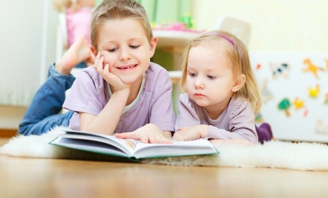 Brother and his little sister at home reading