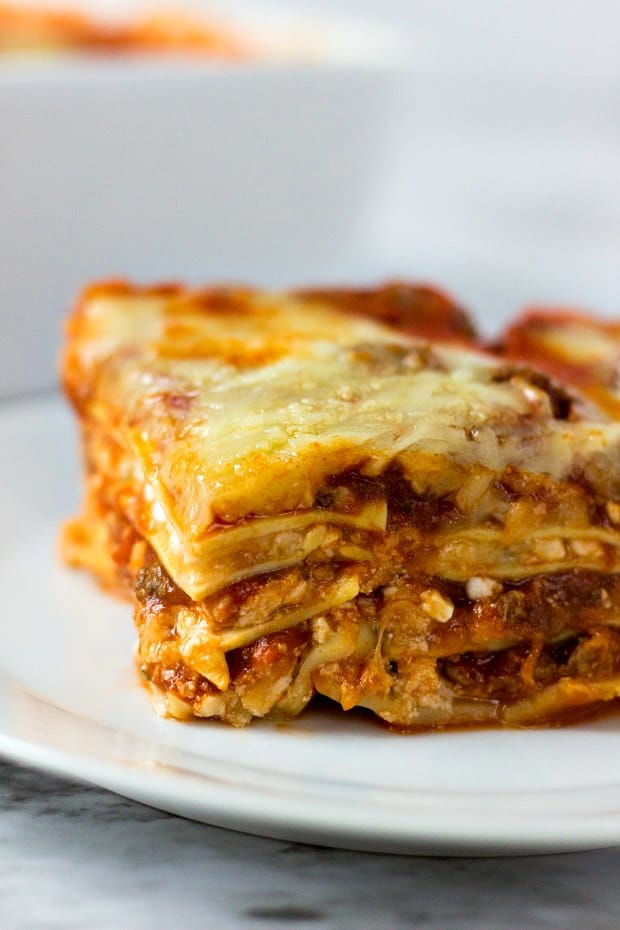 A close up of a plate of food with a slice of pizza, with Cheese and Pasta
