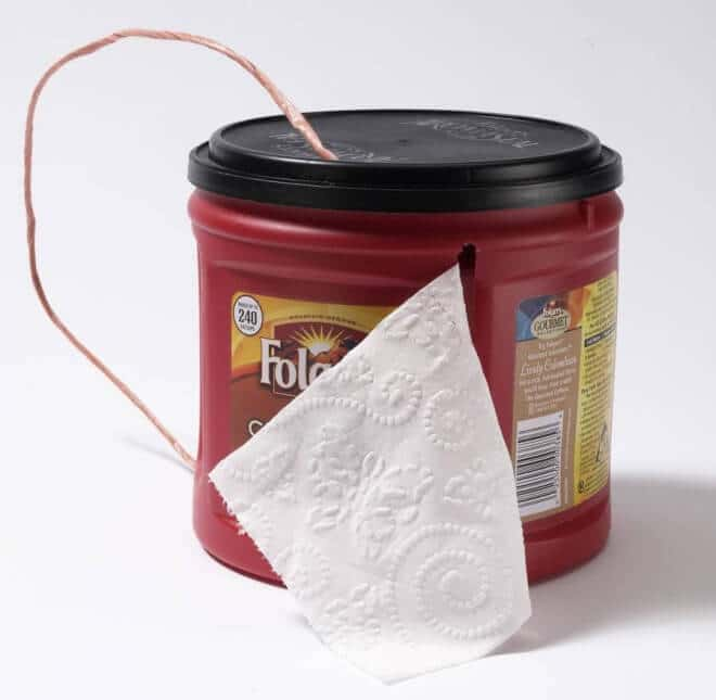 Make a DIY toilet paper holder using an old plastic tub - ideal for camping.