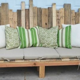 A green sofa in a living room with wooden seat