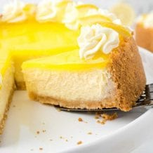 close up shot of lemon cheesecake with a slice being removed with a spatula