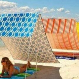 A person sitting at a beach umbrella in the sand