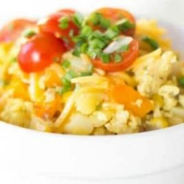 A bowl of food on a plate, with Scrambled eggs