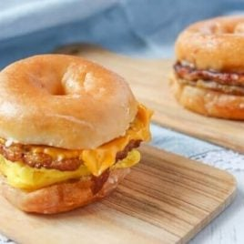 A doughnut sitting on top of a wooden cutting board, with Breakfast sandwich