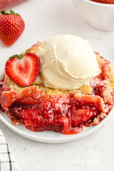 close up shot of strawberry cobbler on a white plate topped with a strawberry and vanilla ice cream