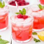 A close up of a glass of orange juice, with Lemonade and Raspberry