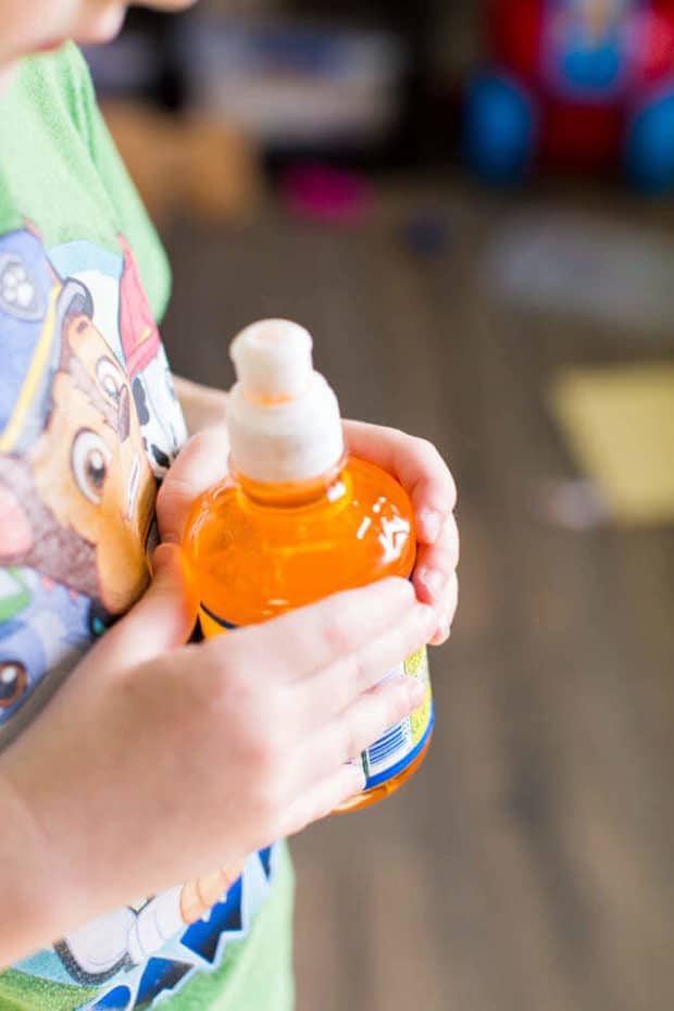 A close up of a person holding a bottle