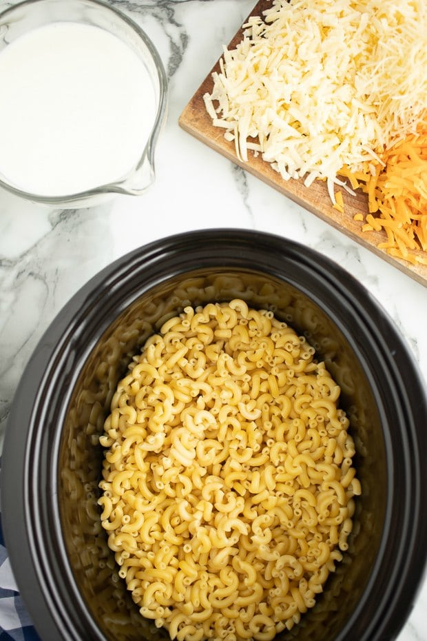 A bowl of rice on a plate, with Cheese and Slow cooker
