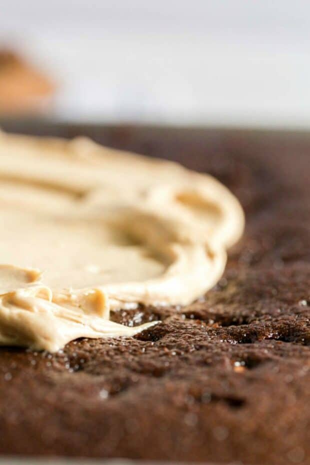 peanut butter frosting being spread on chocolate texas sheet cake