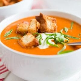A bowl of food on a plate, with Soup and Tomato