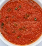 A close up of a bowl of soup, with Sauce and Tomato