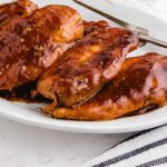 close up shot of slow cooker Coca Cola chicken topped with bbq sauce on a white plate