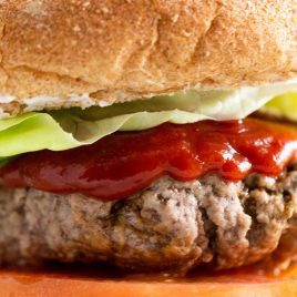 close up shot of the best burger filled with lettuce, tomato, and ketchup