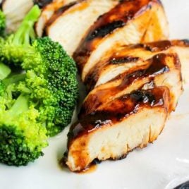 close up shot of a plate of easy grilled chicken with beer marinade topped with bbq sauce and served with a side of broccoli