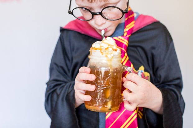 A person drinking from a glass, with Harry Potter and Butterbeer