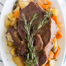 close up overhead shot of instant pot pot roast served over carrots and potatoes on a plate with a piece of thyme on top