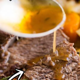 close up shot of instant pot pot roast served over carrots and potatoes with gravy being poured on top
