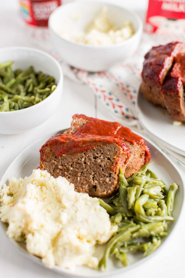 slice of meatloaf on plate with potatoes and green beans