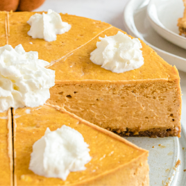 close up shot of pumpkin cheesecake with gingersnap crust with whipped cream on top on a tray