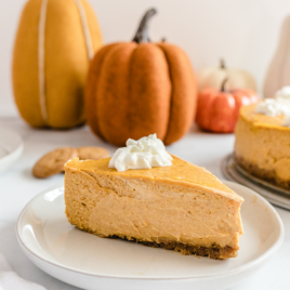 pumpkin cheesecake with gingersnap crust with whipped cream on top on a white plate with pumpkins in background