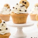 cookie dough cupcakes topped with whipped cream frosting and a mini chocolate chip cookie on a stand