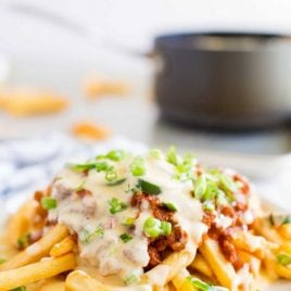 close up shot of Chili Cheese Fries garnished with green onions on a plate