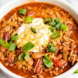 close up shot of a bowl of Turkey Chili topped with sour cream and cheddar cheese then garnished with green onions