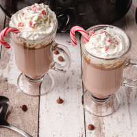 close up shot of crockpot peppermint hot chocolate with whipped cream and candy cane on top