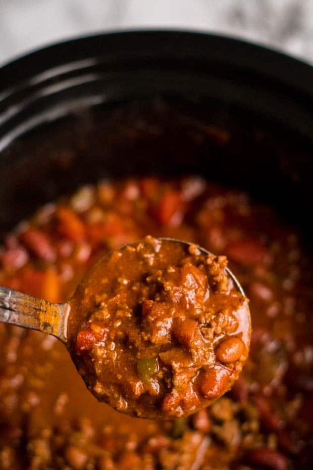 spoon full of chili above slow cooker