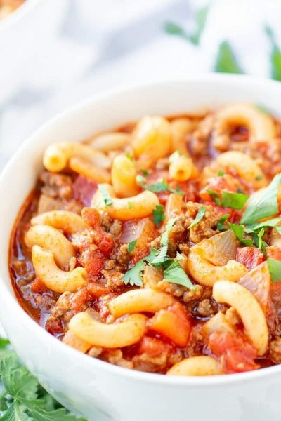 A bowl of food on a plate, with Goulash