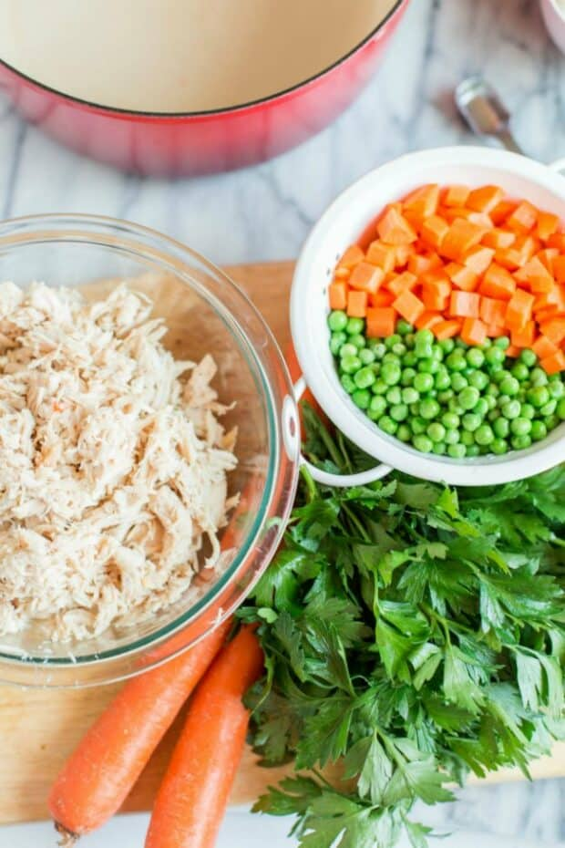 chopped carrots peas and chicken in ingredient bowls