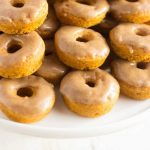 close up shot of pumpkin donuts stacked on top of each other on a plate