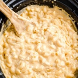 close up shot of Crockpot Mac and Cheese in a crockpot with a large wooden spoon