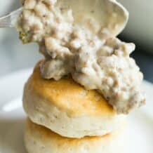 sausage gravy being spooned on biscuits