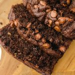 close up shot of slices of chocolate zucchini bread with chocolate chips on a wooden board