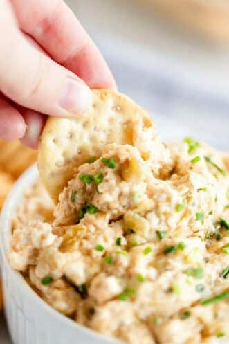 cracker being dipped into hot crab dip