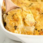 scalloped potatoes on wooden spoon