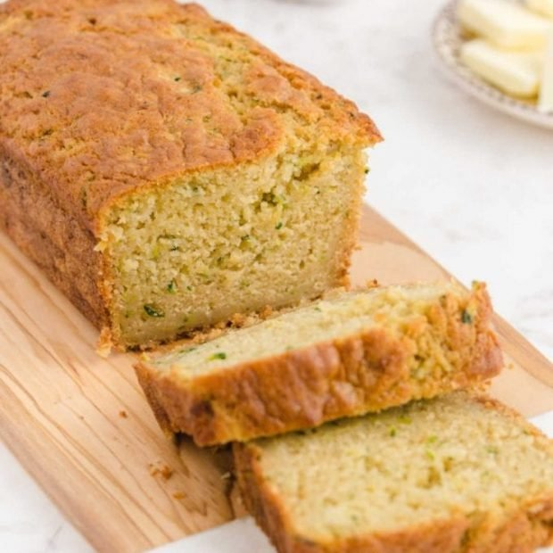 a loaf of zucchini bread sliced on a wooden board