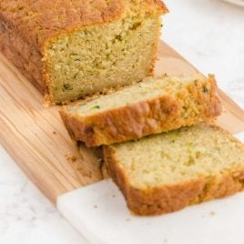 close up shot of a loaf of zucchini bread sliced on a wooden board
