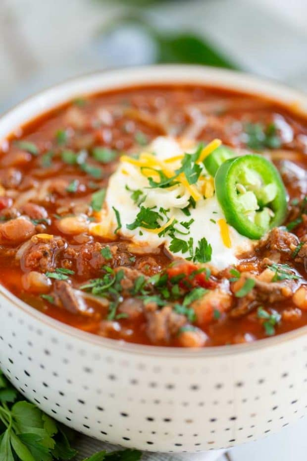 bowl of beef and bean chili with sour cream and jalapenos on top
