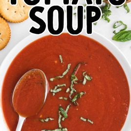 close up overhead shot of a bowl of homemade tomato soup recipe topped with basil served with a spoon
