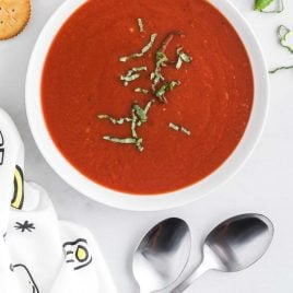close up overhead shot of a bowl of homemade tomato soup recipe topped with basil