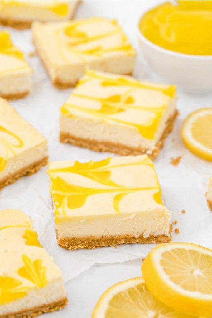 close up shot of lemon cheesecake bars with lemon slices