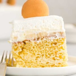 close up shot of a slice of Banana Pudding Cake topped with a vanilla wafer on a plate