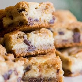close up shot of Chocolate Chip Cheesecake Bars stacked on top of each other